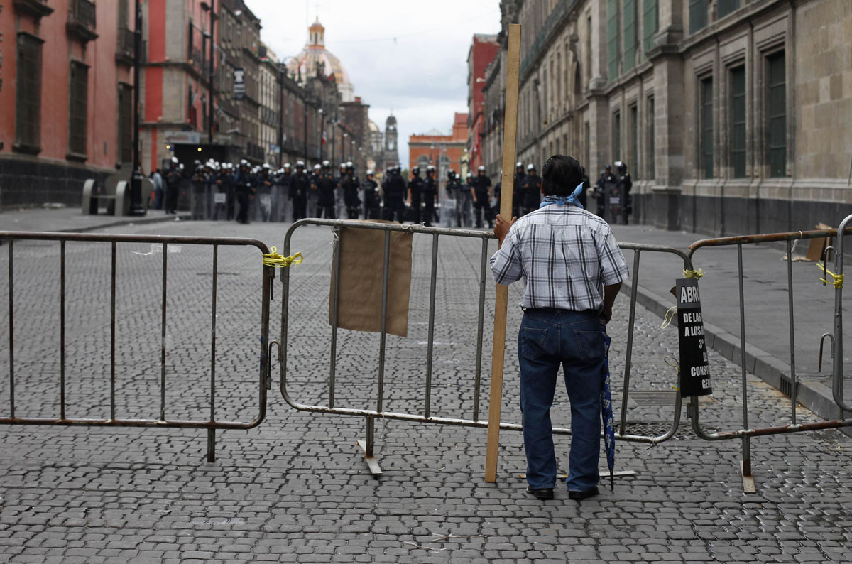 A lone protester stands behind a barricade while holding onto a piece of wood near the Zocalo in Mexico City